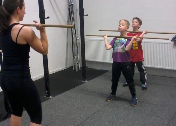 Coach Eva bring den Kids den Thruster in der CrossFit Kids Stunde bei.